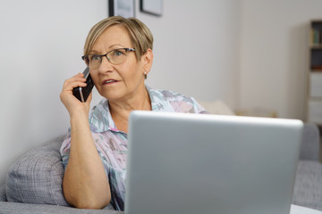 ältere frau mit laptop und telefon