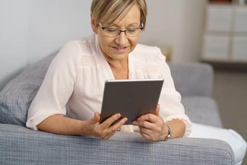 ältere frau liest ein ebook auf dem sofa