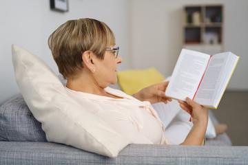 frau sitzt entspannt auf der couch und liest