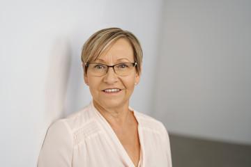 glückliche, ältere frau mit kurzen haaren und brille