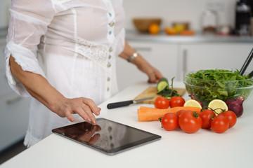 ältere frau steht in der küche und sucht ein rezept im internet