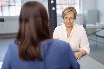 ältere geschäftsfrau schaut eine kollegin ernst an