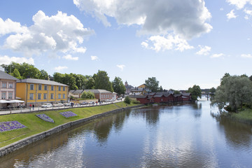 Beautiful scenery in the countryside next to a river in Finland. Sunny summer day with some clouds in the sky. Traditional village view.