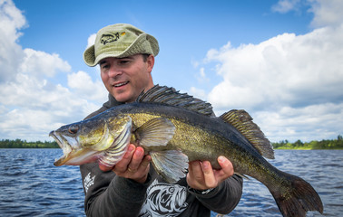 Happy angler with old walleye fish