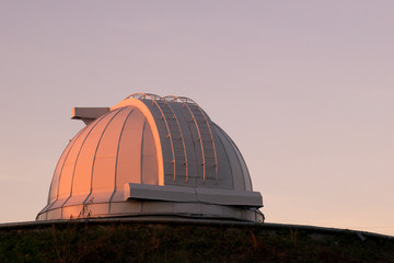 White dome of a large telescope in the Observatory at sunset