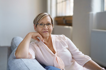 entspannte ältere frau auf ihrem sofa