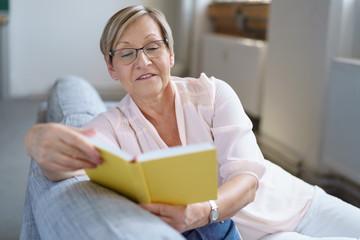 best-agerin liest entspannt auf dem sofa