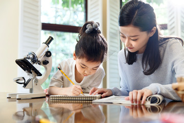 Mother assisting daughter doing homework at table