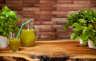 Fresh organic green smoothie with spinach, cucumber, parsley, celery on wooden background