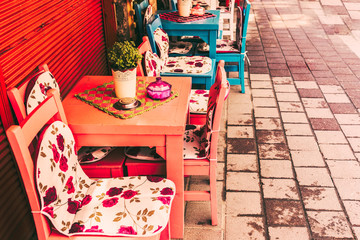 ISTANBUL, TURKEY - May 6, 2017: Interior Retro, vintage view of Pastel coffee shop with wooden tables and chairs in Balat, old town of Istanbul, Turkey. Outdoor cafe. Photo in vintage image style.