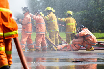 Firefighters spray water in fire-extinguishers and save lives at the gas station. In the midst of spraying.