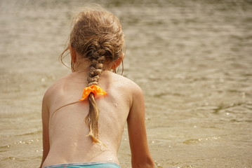 Little girl in the water on the beach during the summer holidays