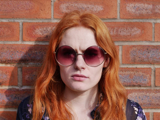 Profile of cute red haired girl with glasses against brick wall