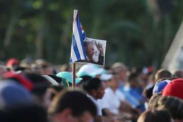 People hold a Cuban flag and a picture of late former Cuban President Fidel Castro during the ceremony marking the 64th anniversary of the July 26, 1953 rebel assault which Castro led on the Moncada army barracks, Pinar del Rio