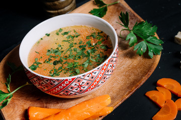 Close up details of traditional chicken soup in bowl and wooden board