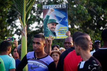 People hold a picture of late former Cuban President Fidel Castro during the ceremony marking the 64th anniversary of the July 26, 1953 rebel assault which Castro led on the Moncada army barracks, Pinar del Rio, Cuba