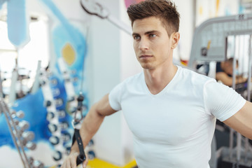 Handsome man training in clean modern gym