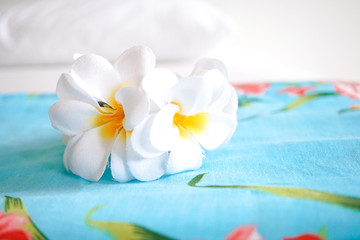 Bali dress (in blue with flower pattern) and artificial plumeria flower crown on the bed. Concept of summer vacation. Hotel complimentary, room in a hotel. Soft window light.