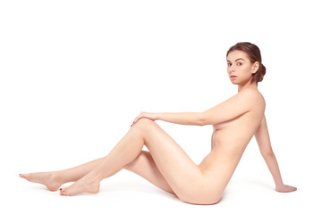 Beautiful young naked brunette woman lying over the background