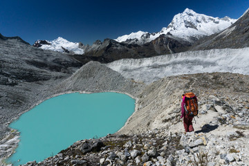 single female mountain climber with large backpack near a turquoise mountain lake while descending from a high altitude peak in the Cordillera Blanca in the Andes in Peru