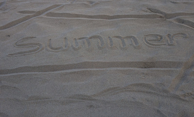 The word summer written on the gray sand on the beach coastline during vacation by the sea in the early morning in summer.