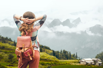 Hipster traveler with backpack enjoying view at mountains in fog.