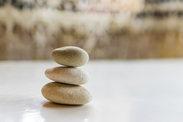 Massage stones, harmony concept and balance in nature. Bokeh background in soft beige tones. Shallow depth of focus. Concept spa and relaxation.