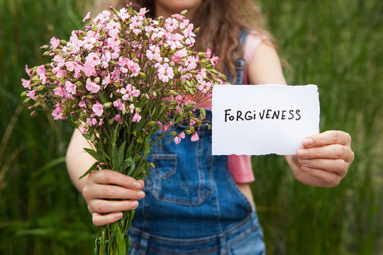 Forgiveness - woman with word and bouquet of pink flowers