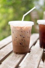 Iced coco or chocolate with straw in plastic cup