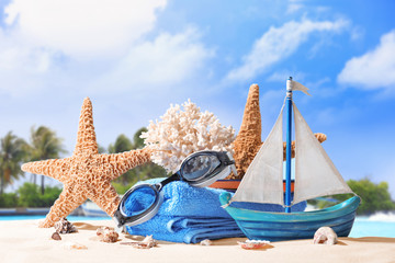 Composition with beach accessories on sea shore. Summer vacation concept