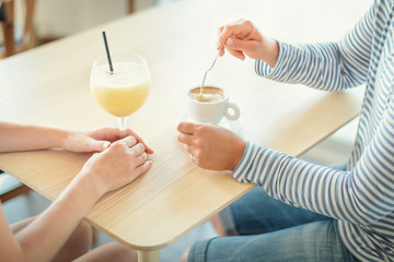 Women talking while drinking coffee and smoothie at cafe. Close-up shot of female hands with beverages on table at cafe