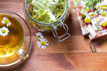 Tea herbs healing chamomile cup wooden background