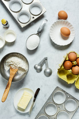 Ingredients (Butter, Eggs, Sugar, Flour, Vanilla) for Baking Cupcakes or Muffins in Kitchen on Marble Counter Top