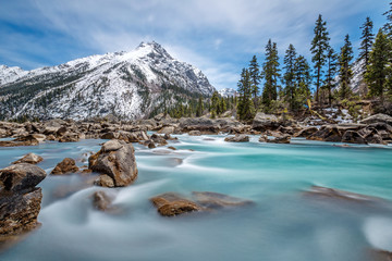 Turquoise creek with snowcapped mountain in background