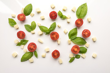 Tomatoes, cheese, Basil on a white background. Ingredients for pizza. Cute simple background, backdrop products of small size. Top view. Close-up. Stock photo Cooking concept.