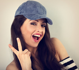 Young crazy happy female model in blue hat showing victory gesture. Closeup toned portrait