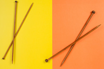 Brown wooden knitting needles on yellow and orange background