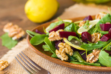Salad with arugula, beets and nuts In a glass jar in a wooden plate