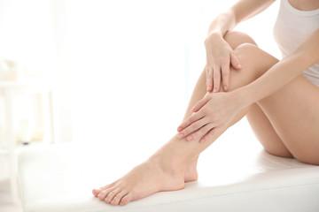 Young woman touching smooth skin on leg, indoors. Epilation concept