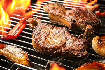 Wall Mural - Delicious steak with vegetables on grilling grid and flame, closeup