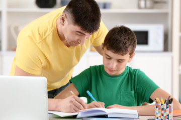 Father and son doing homework together indoors