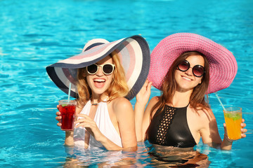 Two beautiful women with cocktails relaxing in pool