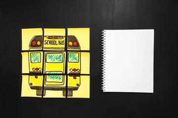 "Back to school background with title ""Back to school"" and ""school bus"" written on the yellow pieces of paper and notebook for yout text are on the chalkboard"