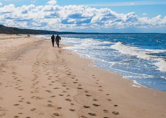 Couple is walking along the beach under blue sky