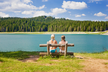 two girls on a bench near the lake