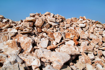 Brown Granite. Big pile of rocks for construction and boulders piled in a heap under a blue sky in summer time. A large pile of limestone in quarry. Pile of gravel and construction material.