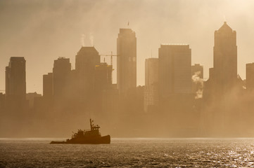 Tug Boat on Elliott Bay on a Foggy Morning. The Seattle skyline is silhouetted as a tugboat works the waters of Elliott Bay during a glorious foggy sunrise.
