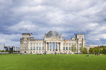 Reichstag building, German Parliament, and people enjoying a summer holiday on the lawn. The dedication Dem deutschen Volke, To the German people, on the frieze
