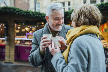 Elderly Couple Drinking Hot Drinks at Christmas Market