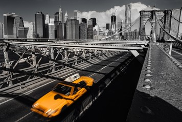 A yellow cab on the brooklyn bridge leaving Manhattan, NYC